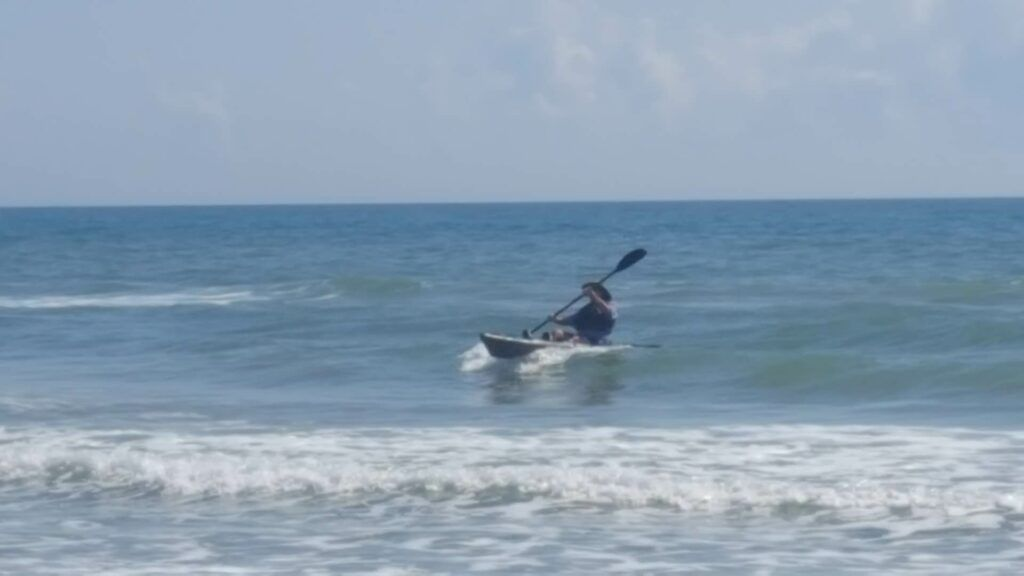 kayak riding the surf back to the beach