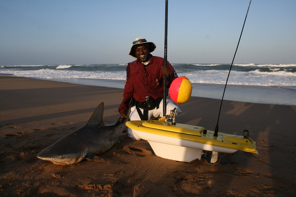 Man with a shark caught from the beach using the Aqua Cat Turbo X Bait Boat