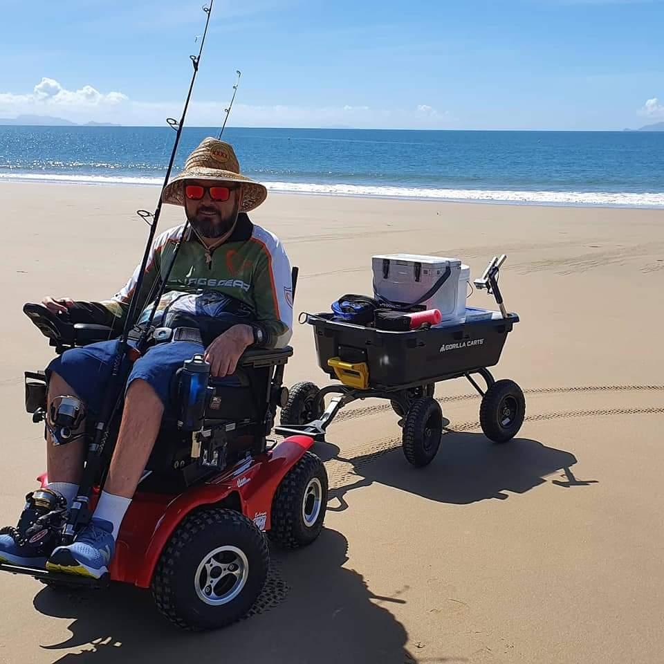 Man in a motorized wheel chair pulling a beach cart - Fish N Mate beach cart review