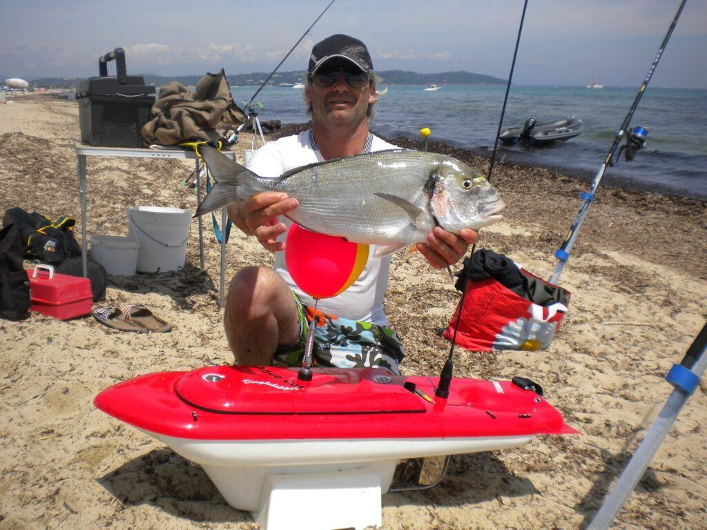 fisherman with a fish he caught using the Aqua Cat Turbo X RC Bait Boat